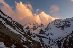 Mountain peaks covered with snow with bright clouds in the evening at sunset against the blue sky stock images