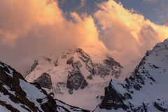 Mountain peaks covered with snow with bright clouds in the evening at sunset against the blue sky stock photos