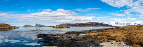 Mountain peaks covered with snow, islands and ocean in northern Norway. Sommaroy Stock Photo
