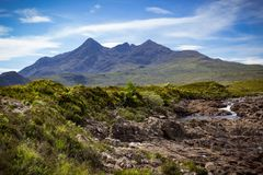 Mountain peaks of Cuillin and a meandering stream landscape royalty free stock image