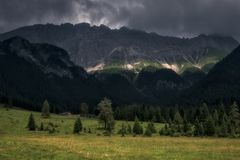 Hut and meadow under mountain range in austria royalty free stock photo