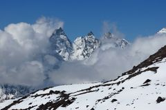 Mountain peaks in the Gokyo Valley reaching ot of clouds Stock Image