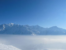 Mountain peaks rise above the clouds. Mountain peaks above the clouds  with bright blue sky, les Contamines, French alps Stock Images