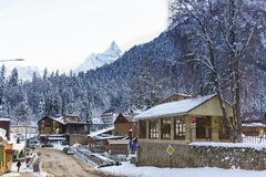 Mountain peaks rise above Karachay Street and the bridge over the Amanauz river in the resort village. Winter day stock image