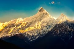 Mountain peaks with snow and blue sky at colorful sunset with sunrays, Himalayas, Nepal stock photo