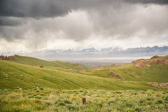 Mountain peaks with snow in the distance, green pastures under dark cloudy sky in Kyrgyzstan. Mountain peaks with snow in the distance, green alpine pastures Stock Photography