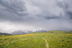 Mountain peaks with snow and green pastures under dark cloudy sky in the At Bashi, Kyrgyzstan. Mountain peaks with snow and green pastures under dark cloudy sky Royalty Free Stock Photos