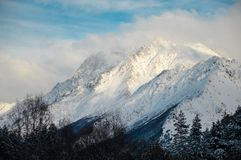 Mountain peaks in the snow with hanging clouds royalty free stock photos