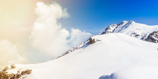 Mountain peaks in winter time. With clouds royalty free stock image