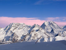 Mountain picks in the Alps. With pink clouds in the background royalty free stock images
