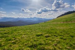 Mountain plain is illuminated by the sun and the mountains are far away. Carpathians Royalty Free Stock Photo