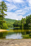 Mountain pond with kayak under a blue sky. Scenic mountain pond where you can kayak and swim in New Hampshire Stock Photography
