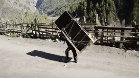 Mountain porter carrying heavy load in Himalayas, Nepal stock video