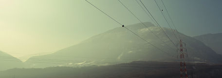 Mountain power lines. Panoramic shot of power lines and red and white pole over a mountain background. Copyspace Stock Photo