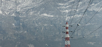 Mountain power lines. Power lines and red and white pole over a mountain background. Copyspace Royalty Free Stock Photo