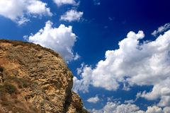 Mountain and puffy white cloud. In the blue sky Royalty Free Stock Image