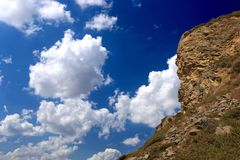 Mountain and puffy white cloud. In the blue sky Stock Photos