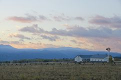Mountain Ranch at Sunrise. A mountain ranch, complete with horse barn and windmill behind a log fence, watches the sun rise behind the Mosquito Mountains Stock Photo