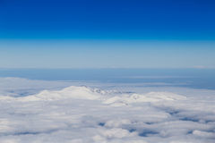 Mountain range emerging from endless white clouds Stock Image