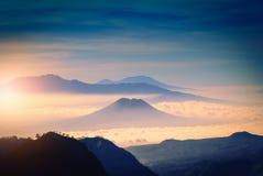 Mountain range in fog with sunlight Stock Photo