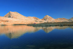 Mountain range with its reflection in the nearby glacial lake stock photos