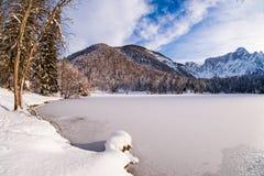 Mountain range Mangart seen from snow covert frozen lake Fusine. With sunbeam Royalty Free Stock Image