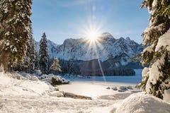 Mountain range Mangart seen from snow covert frozen lake Fusine. With sunbeam Royalty Free Stock Photo