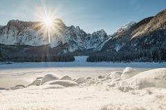 Mountain range Mangart seen from snow covert frozen lake Fusine. With sunbeam Stock Photo