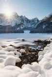 Mountain range Mangart seen from snow covert frozen lake Fusine. With sunbeam Royalty Free Stock Photos