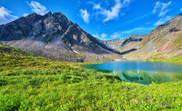 Mountain range near the lake and alpine meadow Royalty Free Stock Images