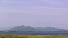 Mountain range over minneriya tank Stock Photos