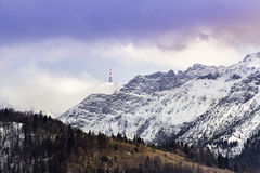 Mountain range with pine trees, snow, clouds and radio antenna stock photography