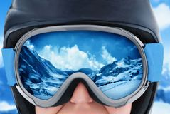 A mountain range reflected in the ski mask. Girl wearing a ski mask. WinterSport, Snowboarding - portrait of young snowboarder girl at the ski resort.A Mountain Royalty Free Stock Image