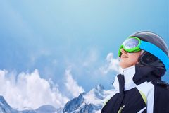 A Mountain Range Reflected in the Ski Mask. An image with a portrait of a female snowboarder wearing a helmet and mask with reflection of snow-capped Alps on the Stock Photos