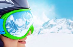 Portrait of young woman at the ski resort on the background of mountains and blue sky.A mountain range reflected in the ski mask. A mountain range reflected in Royalty Free Stock Photos