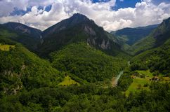 Mountain range and forests of Tara river gorge canyon, Montenegro. Mountain range and small village houses in green forest near Tara river gorge canyon, view royalty free stock image