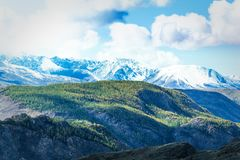 Mountain range with snow-covered peaks under the clouds. Royalty Free Stock Images