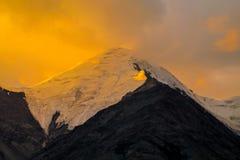 Mountain range snow peaks under orange sunset light royalty free stock photography