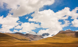 Mountain range on a sunny day is covered with clean white clouds Royalty Free Stock Images