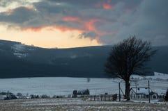 Mountain range at sunset, cloudy sky. Royalty Free Stock Image