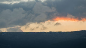 Mountain range at sunset, cloudy sky. Stock Images