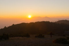 Mountain range sunset with woman. Small in the foreground Royalty Free Stock Photos