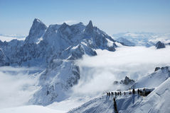 Mountain range between white clouds. Mountain range above layer of white clouds, snow path with mountain-skiers in the foreground, Mont Blanc Royalty Free Stock Photos