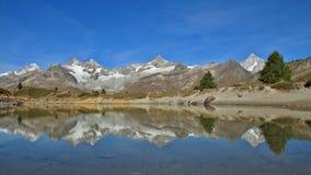 Mountain range in Zermatt mirroring in a lake Royalty Free Stock Image