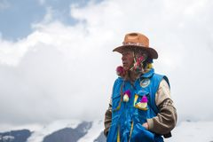Mountain ranger in Peru. VINICUNCA, PERU - OCTOBER 29: mountain ranger in uniform observes surrounding landscape at altitude grounds in Vinicunca, Peru on stock photography