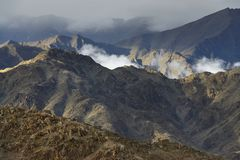 Mountain ranges of brown tones, in the hollows lie clouds, gray sky, autumn in Himalayas. Stock Photography