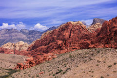 Mountain ranges in Red Rock, Nevada. The rocks are vivid red, orange and dark brown, and show signs of heavy erosion. The sky is b. Lue and cloudy. The landscape Royalty Free Stock Images