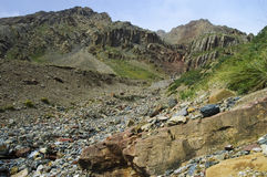 Mountain ravine with a stream and lots of multicol. Ored stones. Terskey mountains, Central Tien-Shan, Kyrgyzstan Stock Images