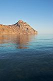 Mountain reflecting in the sea. Karadag mountain in Eastern Crimea at sunset stock photos