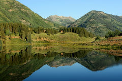 Mountain Reflection. Horizontal view of early morning reflection of mountain scene in clear blue alpine lake Stock Photography